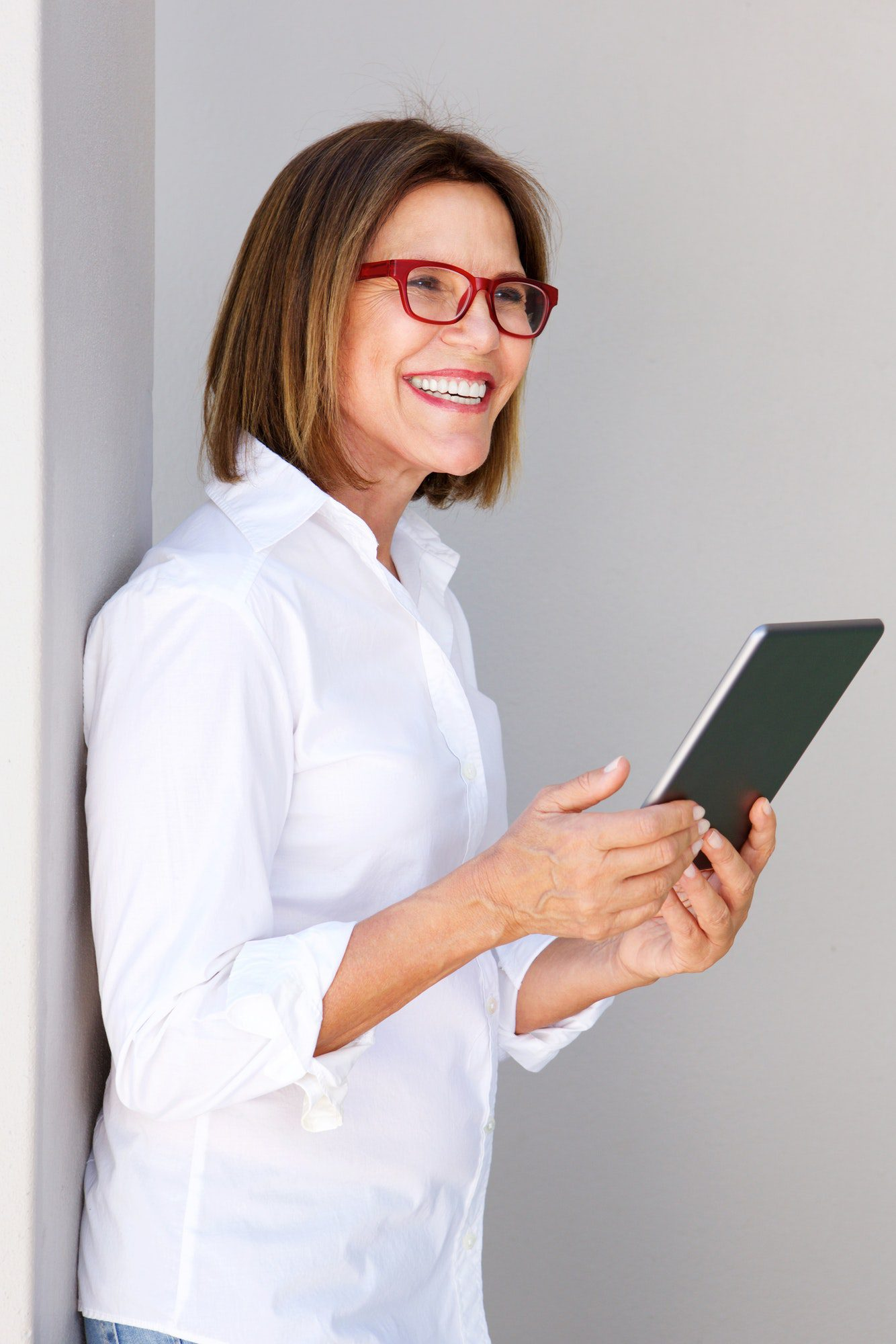 business woman smiling and holding digital tablet