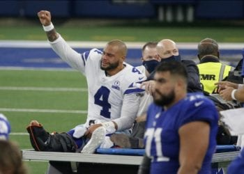 Dallas Cowboys quarterback Dak Prescott (4) lifts his fist to cheers from fans as he is carted off the field after suffering a lower right leg injury running the ball in the second half of an NFL football game against the New York Giants in Arlington, Texas, Sunday, Oct. 11, 2020. (AP Photo/Michael Ainsworth)